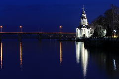 Beautiful Christian church on the banks of the river in the evening , with illumination , lights reflected in water. Stock Photos