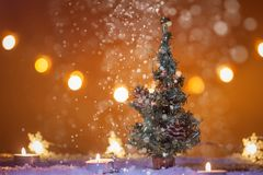 Christmas background with Christmas tree, candles, snow, snowflakes and bokeh lights, snowing panorama Royalty Free Stock Images