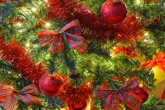Beautiful Christmas background. Beautiful Christmas decoration as a background - illumination of lights and red bows and baubles on a Christmas tree in close-up Stock Photography