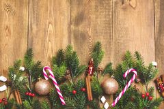 Beautiful Christmas background Wooden Copy space Candy cane Cinnamon Fir branches Top view Christmas toys. Beautiful Christmas background Wooden Copy space Candy royalty free stock photography
