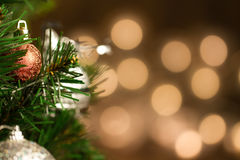 Beautiful Christmas ball on the defocused background of yellow lights. Royalty Free Stock Photos