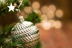 Beautiful Christmas ball on the defocused background of yellow lights. Stock Image