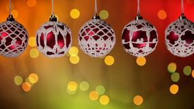 Beautiful christmas baubles hanging against blinking xmas lights background stock footage