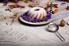 A freshly baked holiday`s cake with sugar powder and violet flowers on a gray background. Decoration for Christmas. stock image