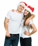 Beautiful Christmas couple in Santa hats Royalty Free Stock Images