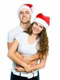 Beautiful Christmas couple in Santa hats Stock Photo