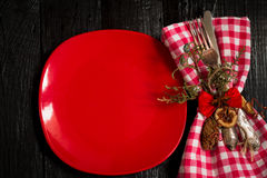 Beautiful Christmas Cutlery on a napkin in red and white checkered with   plate.   black wooden background. Stock Photography