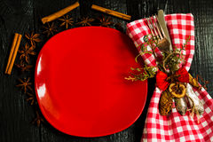 Beautiful Christmas Cutlery on a napkin in red and white checkered with   plate.   black wooden background. Royalty Free Stock Image