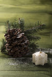 Beautiful christmas decoration, candle, cone and pine branch. Beautiful christmas decoration, on the green background Stock Photo