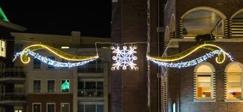 Beautiful christmas decoration with lights hanging between some buildings in the city streets at night time. A Beautiful christmas decoration with lights hanging royalty free stock photos