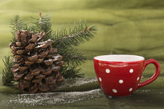 Beautiful christmas decoration, with red polka dot cup, cone, and pine branch. Beautiful christmas decoration, on the green background Royalty Free Stock Image