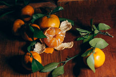 Beautiful Christmas decoration with tangerines in the night light garlands. Citrus still life. The symbol of the new year Stock Photo