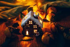 Beautiful Christmas decoration with tangerines and a toy house in the night light garlands. Citrus still life Stock Image