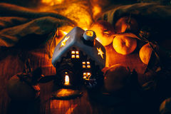 Beautiful Christmas decoration with tangerines and a toy house in the night light garlands. Citrus still life Stock Photo