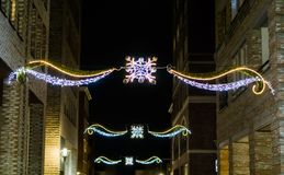 Beautiful christmas decorations hanging between the buildings in the city streets at night. Some beautiful christmas decorations hanging between the buildings in stock image