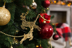 Beautiful Christmas deer toys, balls and garlands hanging on Chr. Istmas tree in the living room Stock Photography