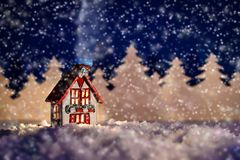 Christmas fairy-tale picture of a winter house. Beautiful Christmas fairy-tale picture of a winter cabin in a forest at night in the snow Royalty Free Stock Images