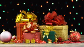 Beautiful Christmas gift boxes and decorations on a wooden floor against colorful flashing garland on black background
