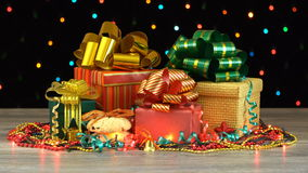 Beautiful Christmas gift boxes and decorations on a wooden floor against colorful flashing garland on a black background. Seamless stock video footage