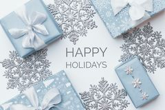 Beautiful christmas gifts and silver snowflakes isolated on white background. Pastel blue colored wrapped xmas boxes. Gift wrapping concept stock image