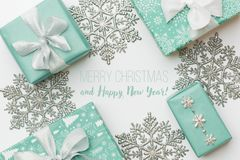 Beautiful christmas gifts and silver snowflakes isolated on white background. Turquoise colored wrapped xmas boxes. Gift wrapping concept royalty free stock photo