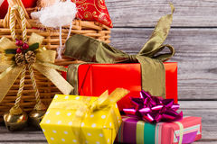 Beautiful Christmas gifts and wicker basket on the wooden backgr. Ound. Preparing for the New Year holidays Royalty Free Stock Image