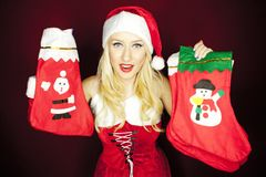 Beautiful Christmas girl with Christmas stockings. Beautiful blonde model dressed in Christmas outfit holding Christmas stockings, on a red background Royalty Free Stock Photo