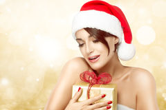Beautiful Christmas girl clasping a gift Stock Photos