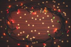Beautiful christmas glowing garland with golden star confetti on the wooden table top view toned background copy space. Beautiful christmas glowing garland with royalty free stock image