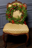 Beautiful Christmas green festive wreath from the Christmas tree lying on a chair Stock Photos