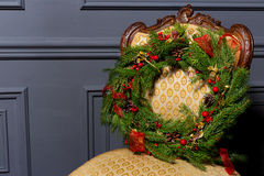 Beautiful Christmas green festive wreath from the Christmas tree lying on a chair Royalty Free Stock Photography