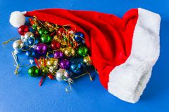 Beautiful Christmas hat, presents and Christmas balls on a red cap. stock photo