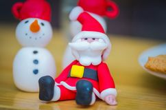Beautiful christmas holiday fondant figurines. Nice snowman.santa claus and gingerbread cookies in the backround Stock Photography