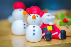 Beautiful christmas holiday fondant figurines. Nice snowman.santa and gingerbread cookies in the backround Stock Photo