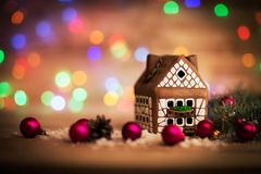 Beautiful Christmas house. With fir paws on wooden background stock photography