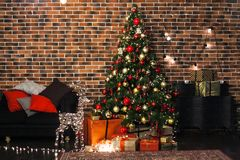 Beautiful Christmas living room with decorated Christmas tree, gifts and deer with the glowing lights at night. New Year stock image
