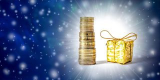 Beautiful Christmas and New Year`s background with coins and gift box in gold packaging. royalty free stock photography