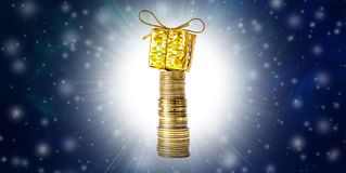 Beautiful Christmas and New Year`s background with coins and gift box in gold packaging, falling snow and free space for text. Beautiful Christmas and New Year` royalty free stock photos