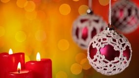 Beautiful christmas ornaments and candles. In front of warm colored blurry xmas lights background - closeup with copyspace stock video footage