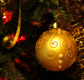 Beautiful Christmas picture with Christmas tree and ball. New Years Eve celebration background with Gold ball decorations. Bokeh gold garland on green  tree Stock Photos