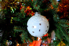 Beautiful Christmas picture with Christmas tree and ball. New Years Eve celebration background with white snow  ball decorations. Bokeh green  tree brunch Royalty Free Stock Photography