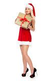 Beautiful christmas Santa girl is holding gift in studio. Royalty Free Stock Photo