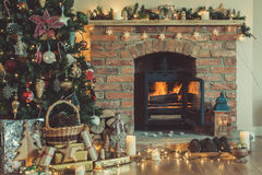 Christmas setting, decorated fireplace, fur tree. Beautiful Christmas setting, decorated fireplace with woodburner, lit up Christmas tree with baubles and Stock Photography