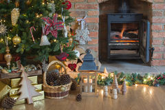 Christmas setting, decorated fireplace, fur tree. Beautiful Christmas setting, decorated lit up Christmas tree with baubles and ornaments, fireplace with Royalty Free Stock Photo