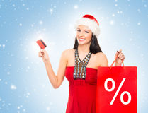 Beautiful Christmas shopper girl holding a business card Royalty Free Stock Photo