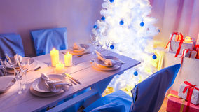 Beautiful Christmas table setting with present and tree Stock Photos
