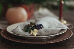 Beautiful christmas table setting with sackcloth rustic napkin, candle and fir tree, close up.  Royalty Free Stock Images