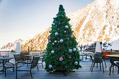 Beautiful Christmas tree decorated with balls and garlands on the background of the mountains in an outdoor cafe in the daylight h. Igh in the mountains royalty free stock photography