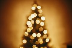 Beautiful christmas tree golden lights in festive room. christmas abstract background, blur defocused bokeh of yellow glowing de. Coration on christmas tree stock image