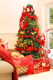 Christmas tree. Beautiful Christmas tree with a Santa hat on top, Christmas elves, a sleigh and pretty presents Royalty Free Stock Images